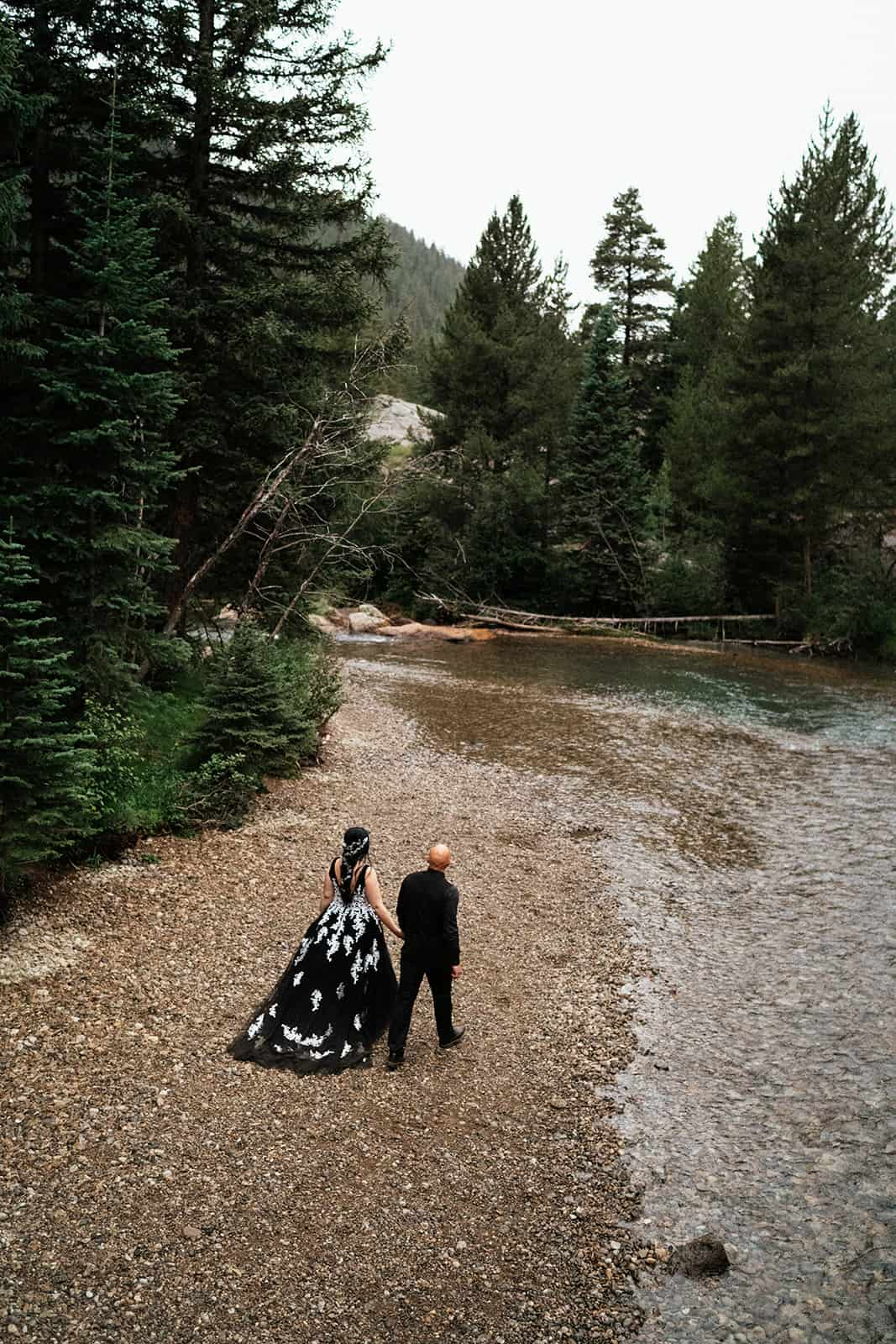 bride and groom walking along river at Colorado elopement