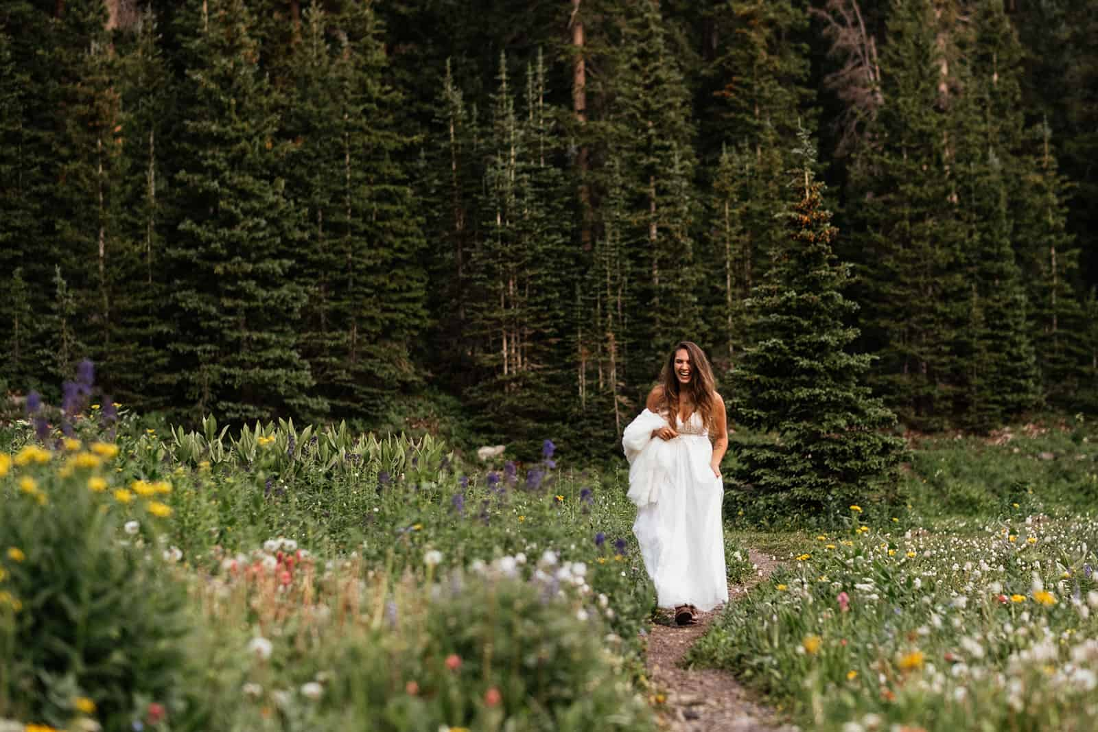 bride walking down aisle of wildflowers at Colorado elopement