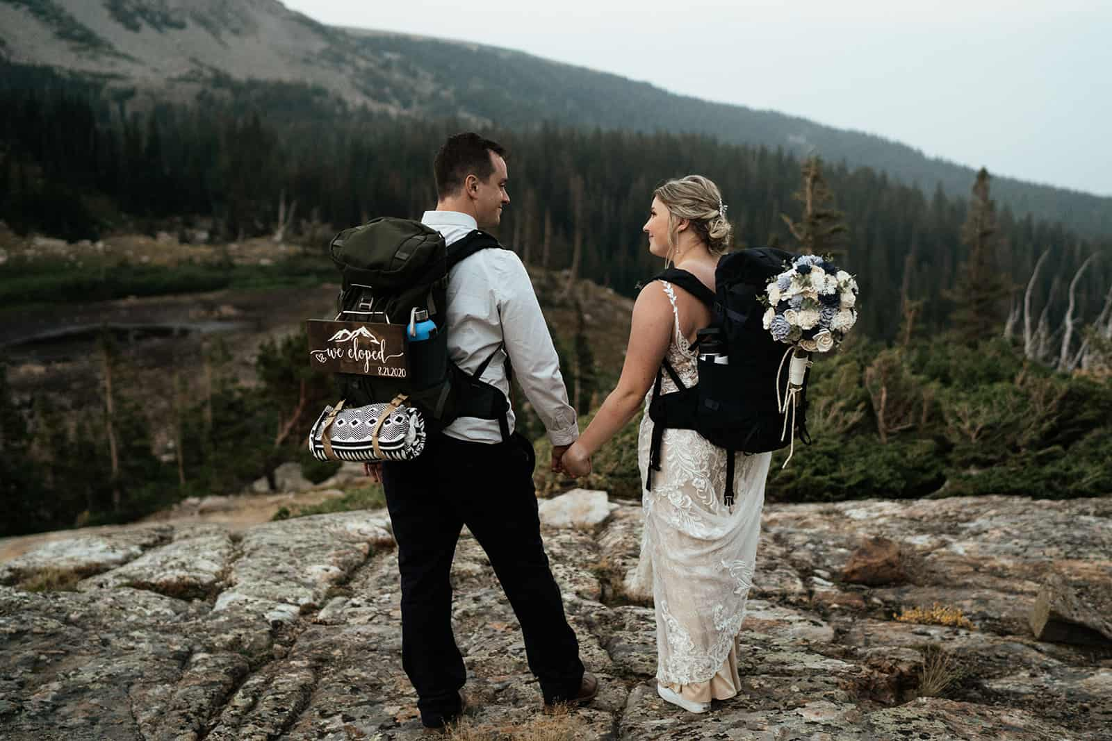 couple wearing backpacks and we eloped sign at colorado elopement