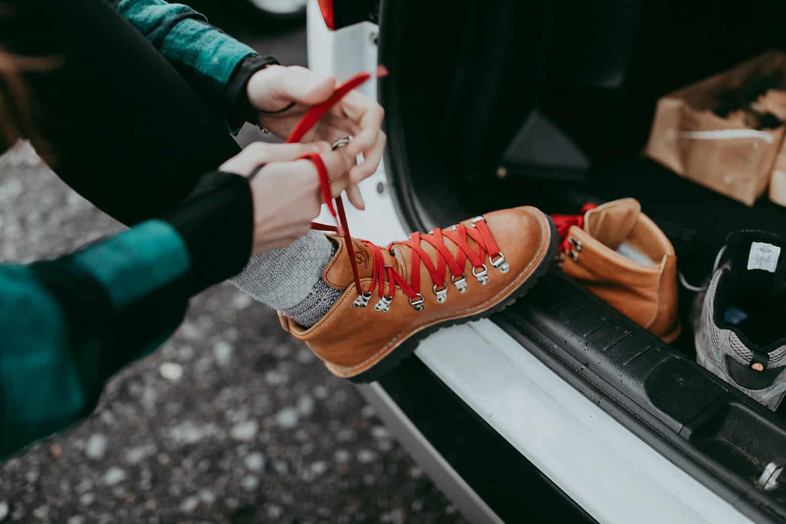 bride tying hiking boots at elopement