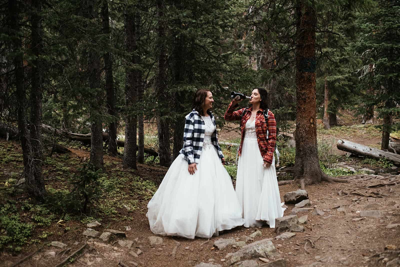 two brides drinking champagne at Colorado hiking elopement